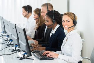 Call center agents in formal attire smiling