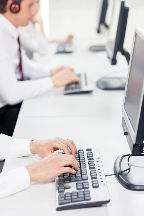 BPO call center agents typing on computer keyboards.